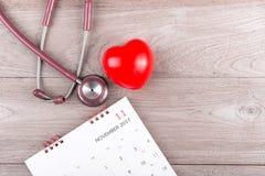 Vérifiez le concept de coeur : Coeur, calendrier et stéthoscope rouges sur le bro Photos stock