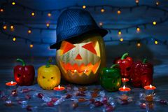 Véspera do ` s de Dia das Bruxas a Jack-o-lanterna em um chapéu e em velas para dentro, scaring a cara ilumina grightening azul i fotos de stock