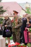 Vétéran avec des fleurs aux soldats tombés de monument Image stock