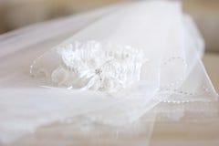 Véu do casamento e uma liga Fotos de Stock Royalty Free
