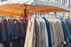 Vêtements à vendre accrochant sur un support au marché aux puces extérieur Images libres de droits