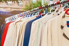Vêtements à vendre accrochant sur un support au marché aux puces extérieur Photographie stock libre de droits