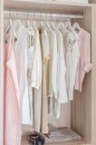 Vêtements accrochant dans la garde-robe en bois image stock