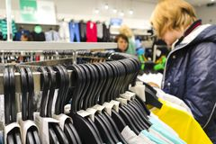 Vêtements accrochant dans une rangée sur les cintres du magasin Une femme choisit des vêtements photo libre de droits