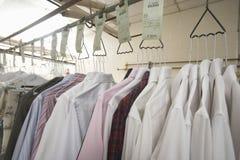 Vêtements accrochant sur le cintre dans la blanchisserie images libres de droits