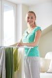 Vêtements accrochants de femme heureuse sur le dessiccateur à la maison photo libre de droits
