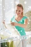 Vêtements accrochants de femme heureuse sur le dessiccateur à la maison image libre de droits