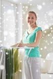 Vêtements accrochants de femme heureuse sur le dessiccateur à la maison image stock