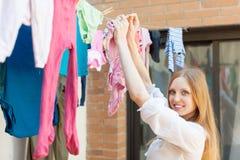 Vêtements accrochants de fille à sécher sur la corde à linge photographie stock
