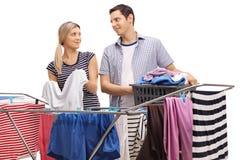Vêtements accrochants de jeunes couples sur un dessiccateur de support ensemble images stock