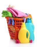 Vêtements avec le détergent dans le panier en plastique orange Photo stock