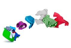 Vêtements colorés lumineux volant de la cuvette de lavage sur le blanc Images libres de droits