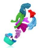 Vêtements colorés lumineux volant de la cuvette de lavage sur le blanc Photographie stock libre de droits