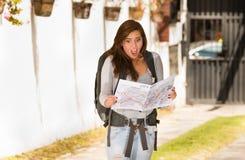 Vêtements décontractés de port et sac à dos de jeune jolie femme se tenant devant l'appareil-photo, regard choqué d'expression du Photographie stock libre de droits