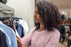 Vêtements d'achats de femme de couleur dans un magasin Photo libre de droits
