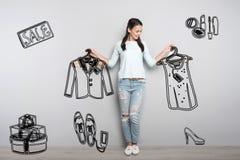 Vêtements de achat de jeune avec la grande remise et regard heureux images stock