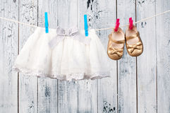 Vêtements de bébé accrochant sur la corde à linge. Photos stock
