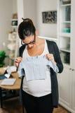 Vêtements de bébé d'achats de femme enceinte de maison Images libres de droits