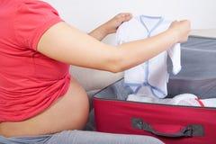 Vêtements de bébé d'emballage de femme enceinte Images stock