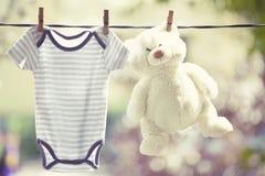 Vêtements de bébé et ours de nounours accrochant sur la corde à linge images libres de droits