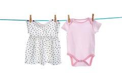 Vêtements de bébé sur la ligne de blanchisserie photos stock