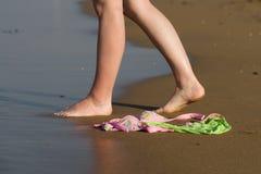 Vêtements de bain sur la plage et le femme marchant à la mer Photographie stock