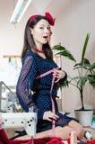Vêtements de couture dans l'atelier : fille de pin-up de belle jeune femme de brune avec les lèvres et les clous rouges, dans la  Photo libre de droits