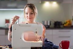 Vêtements de couture de belle jeune femme avec la machine à coudre Photos libres de droits