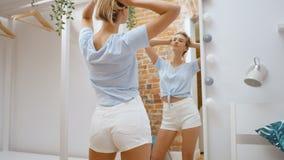 Vêtements de essai de jeune adolescente et regarder le smilng de miroir heureux clips vidéos