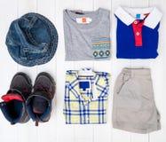 Vêtements de mode de voyage de bébé garçon sur le bois blanc Image libre de droits