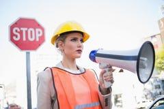 Vêtements de port de froncement de sourcils de constructeurs de femme d'affaires tenant le megaphon Photographie stock