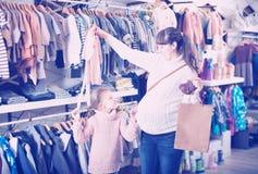 Vêtements de sourire d'exposition de mère pour des bébés Photographie stock