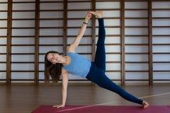 Vêtements de sport blancs de port de jeune jolie femme calme établissant, faisant l'exercice de yoga ou de pilates D'isolement su photographie stock