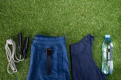 Vêtements de sport bleus, accessoires pour la forme physique et une bouteille de l'eau, dans la perspective de l'herbe, sur des s Images stock