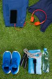 Vêtements de sport bleus, une bouteille de l'eau et accessoires pour la forme physique, dans la perspective de l'herbe Photographie stock libre de droits