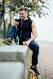 Vêtements de sport de port d'homme de forme physique écoutant la musique se reposant sur un banc en pierre Détendez après la séan Photographie stock libre de droits