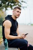 Vêtements de sport de port d'homme de forme physique écoutant la musique se reposant sur un banc en pierre Détendez après la séan Photos stock