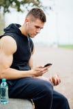 Vêtements de sport de port d'homme de forme physique écoutant la musique se reposant sur un banc en pierre Détendez après la séan Photo libre de droits
