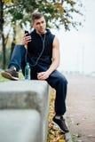 Vêtements de sport de port d'homme de forme physique écoutant la musique se reposant sur un banc en pierre Détendez après la séan Image libre de droits