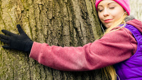 Vêtements de sport de port de femme étreignant l'arbre Image stock