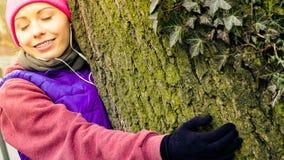 Vêtements de sport de port de femme étreignant l'arbre Images stock