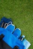 Vêtements de sport et accessoires bleus dans un sac, et une bouteille de l'eau, sur le fond de l'herbe avec un endroit pour l'enr Photo stock