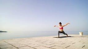 Vêtements de sport de port de femme sportive faisant le yoga sur la promenade de bord de la mer pendant le matin banque de vidéos