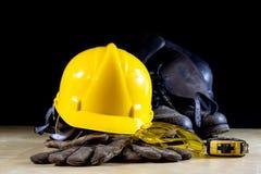 Vêtements de travail, casque, gants et verres sur une table de fonctionnement en bois photo libre de droits