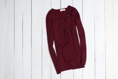 Vêtements et accessoires Chandail rouge avec le laçage sur les planches en bois blanches de plancher Configuration plate photographie stock