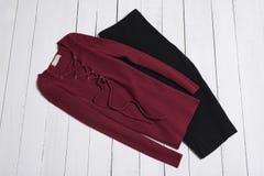 Vêtements et accessoires Jupe noire du Midi et chandail rouge avec le laçage sur les planches en bois blanches de plancher Config photographie stock libre de droits