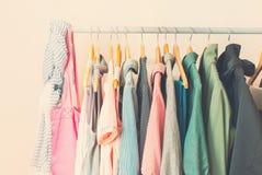 Vêtements femelles de couleur en pastel dans une rangée sur le cintre ouvert toned Photo stock