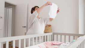 Vêtements heureux de bébé d'arrangement de femme enceinte à la maison clips vidéos