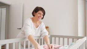 Vêtements heureux de bébé d'arrangement de femme enceinte à la maison banque de vidéos
