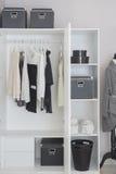 Vêtements noirs et blancs accrochant dans la garde-robe images libres de droits